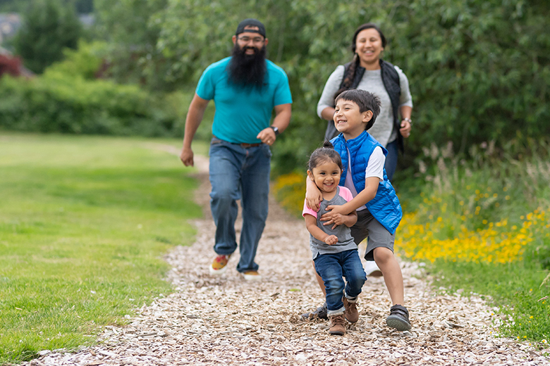 An elementary-age boy and his little sister run along a path out in nature. They're ahead of mom and dad and have big smiles. Big brother is playfully tackling his little sis.