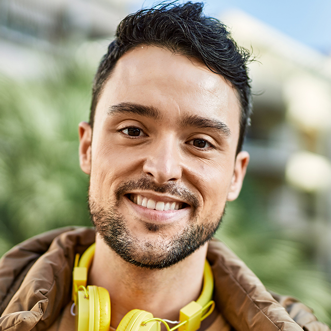 Young hispanic man smiling happy using headphones at the city.